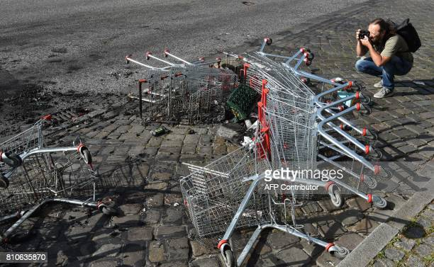 A man takes pictures of shopping carts laying in the street after riots in Hamburg's Schanzenviertel district on July 8 2017 in Hamburg northern...
