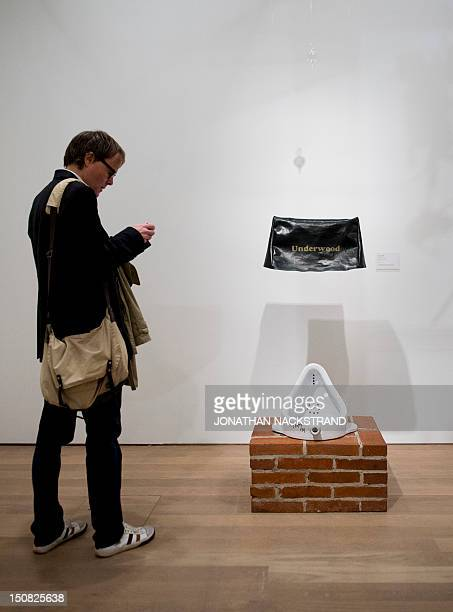 A man takes pictures of the artwork 'Fountain' by French artist Marcel Duchamp during the Picasso/Duchamp 'He was wrong' exhibition at the Moderna...