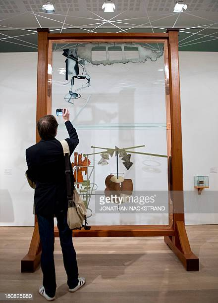 A man takes pictures of the artwork 'The Bride Stripped by Her Bachelors Even' by French artist Marcel Duchamp during the Picasso/Duchamp 'He was...
