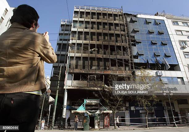 A man takes pictures of the burned Emboriki and Attica banks in central Athens on December 9 2008 Authorities closed off many Athens streets today...