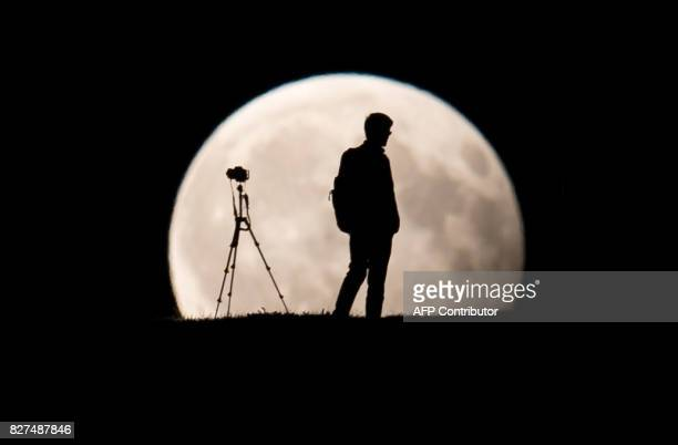 A man takes pictures of the moon standing in a partial lunar eclipse on August 7 2017 in Munich southern Germany / AFP PHOTO / dpa / Sven Hoppe /...