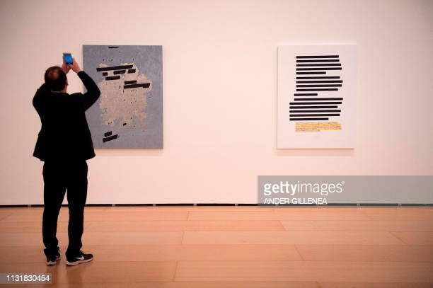A man takes pictures of two artworks from the 'Redaction paintings' series by US artist Jenny Holzer during a presentation of the 'Jenny Holzer Thing...