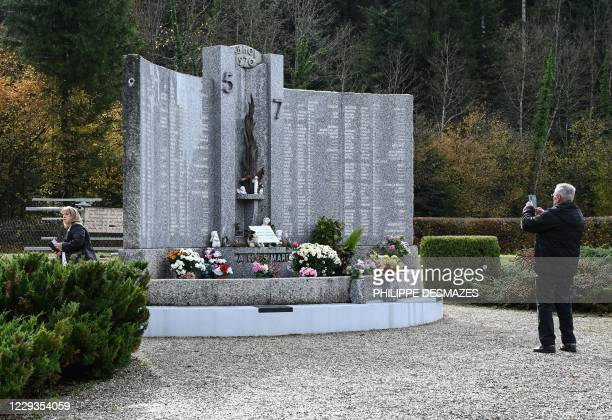 """Man takes pictures on October 29 in Saint-Laurent-du-Pont, south-east France, at a memorial in tribute to the 146 victims of a fire in the """"5-7""""..."""