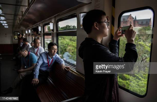 A man takes pictures out the window of a train used by Huawei workers client and other visitors at the company's new sprawling 'Ox Horn' Research and...