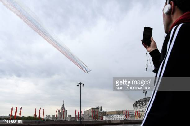 Man takes pictures with his mobile phone of Russian Sukhoi Su-25 assault aircrafts releasing smoke in the colours of the Russian flag during a...