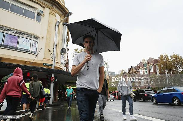 A man takes shelter from the rain as he crosses Crown St Surry Hills on April 4 2015 in Sydney Australia Wet weather has settled in over most of New...