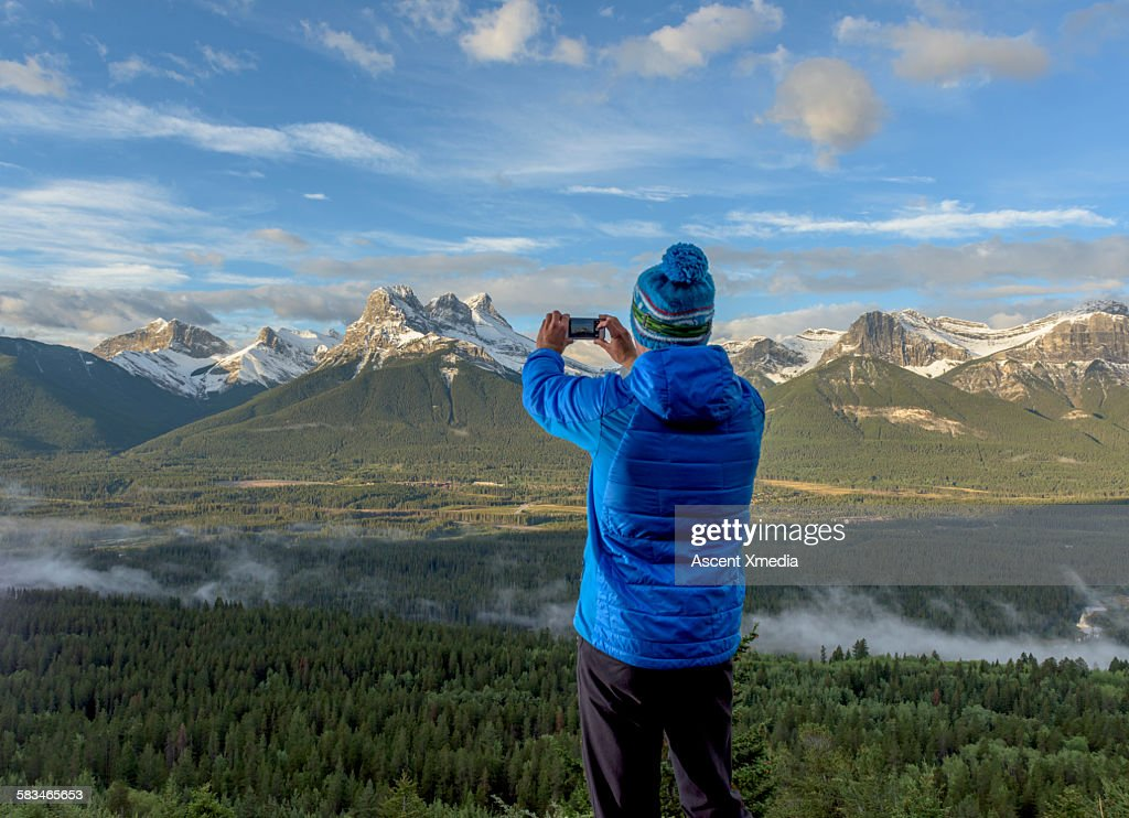Man takes smart phone picture across mtn valley : Stock Photo