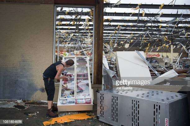 A man takes some tobacco products from a damaged store after hurricane Michael passed through the area on October 10 2018 in Panama City Florida The...