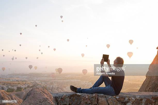 man takes tablet pic of hot air balloons rising - turkey middle east stock pictures, royalty-free photos & images