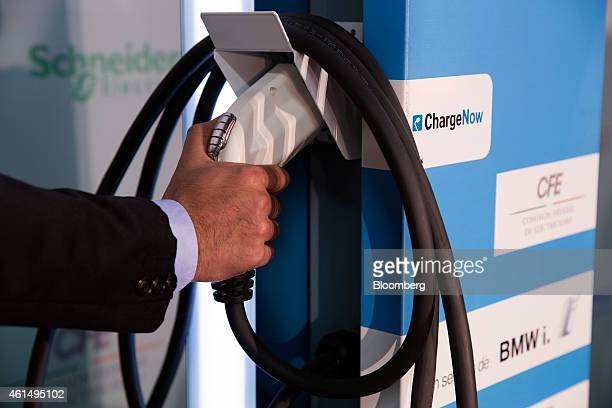 A man takes the electric charger from the charging station during an event in Mexico City Mexico on Tuesday Jan 13 2015 The state of Mexico today...