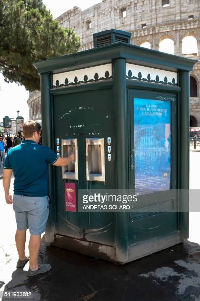 A man takes water from a kiosk designed in the style of the hexagonal newspaper stands in front of the Ancient Colosseum in Rome on June 21 2016...