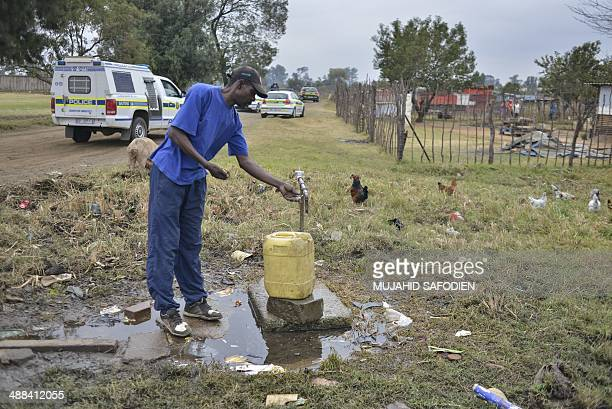 A man takes water while South African police officers patrol aboard vehicles in the restive township of Gugulethu early morning on May 6 2014 South...