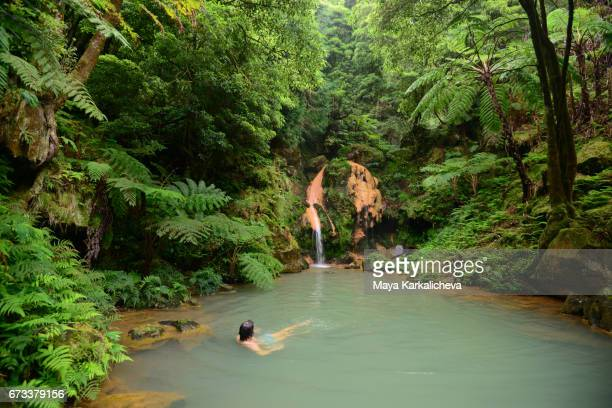 man taking a bath in a hot waterfall, caldeira velha hot springs, azores island - las azores fotografías e imágenes de stock