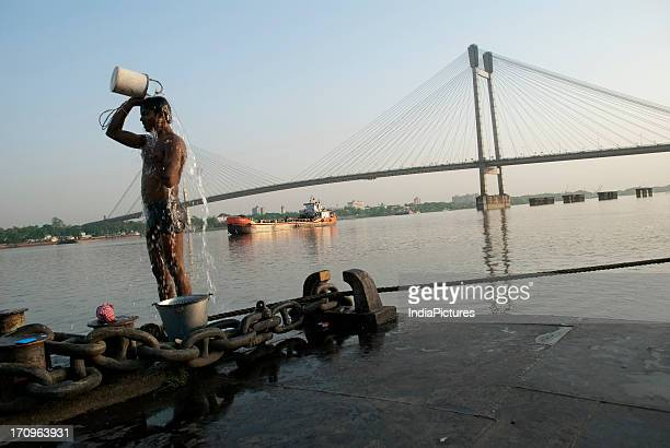 Man taking a bath near Hooghly river with the Second Hooghly Bridge in the backdrop Kolkata West Bengal India
