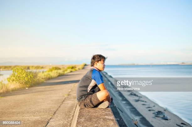A man taking a break at the top of breakwater