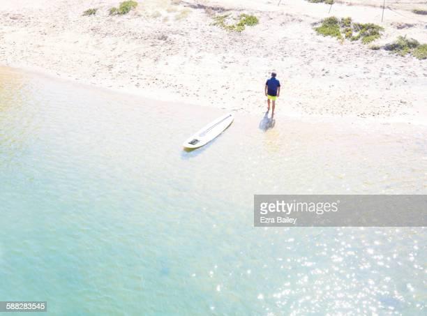 Man taking a break from paddleboarding in the sun