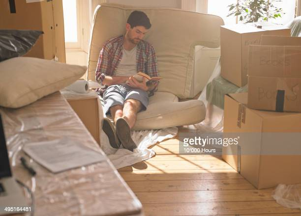 Man taking a break from unpacking in his new home
