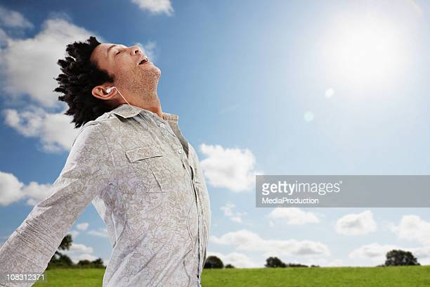 man taking a deep breathe outdoors