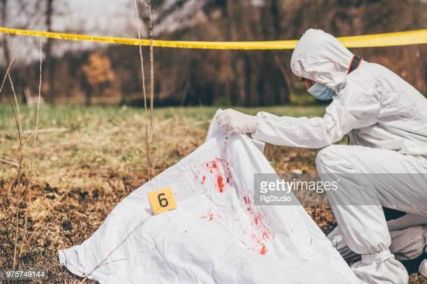 man taking a glance at dead body under the sheet on the crime scene - dead body imagens e fotografias de stock