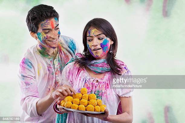 man taking a laddoo from a tray - new generation stock pictures, royalty-free photos & images