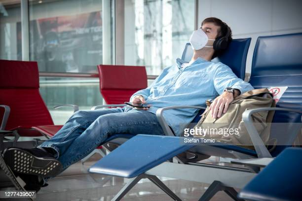 man taking a nap in the airport lobby wearing surgical face mask - human body part stock pictures, royalty-free photos & images