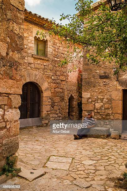 Man taking a nap sitting in a narrow stoned street in a Mediterranean rural Catalan town
