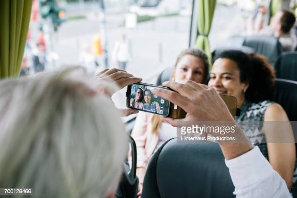 Man Taking A Photo For Two Woman Traveling On Bus