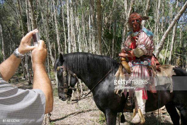A man taking a photo of a man on a horse at the Big Cypress Shootout event at Billie Swamp Safari