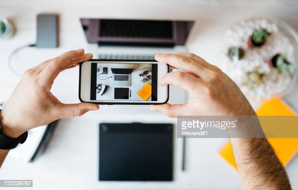 Man taking a photo of his desktop with smartphone, top view