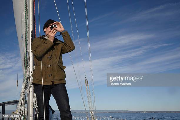 Man taking a photo on a sailboat