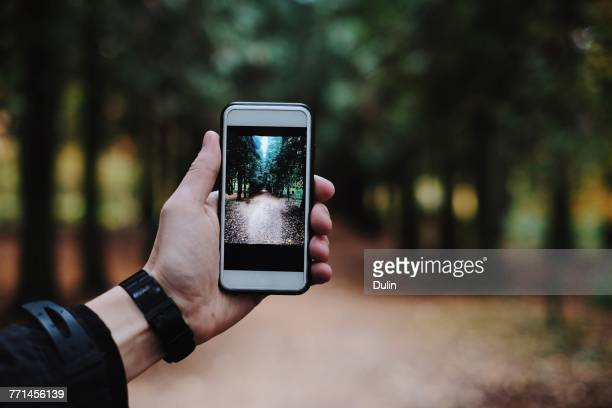 man taking a photo with a smartphone - photo messaging stock photos and pictures