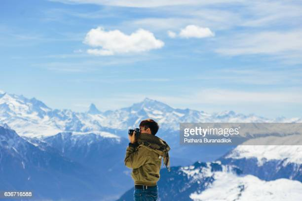 A Man taking a photo with the background of Alps