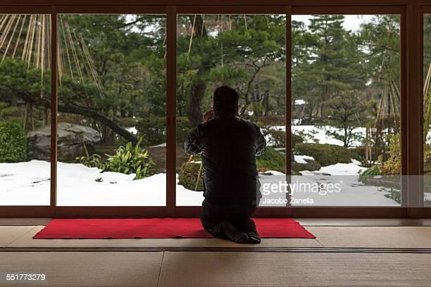Man taking a photograph of a Japanese garden
