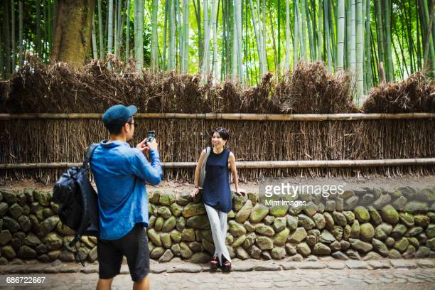 a man taking a photograph of a woman by a fence around woodland. - capturing an image stock pictures, royalty-free photos & images