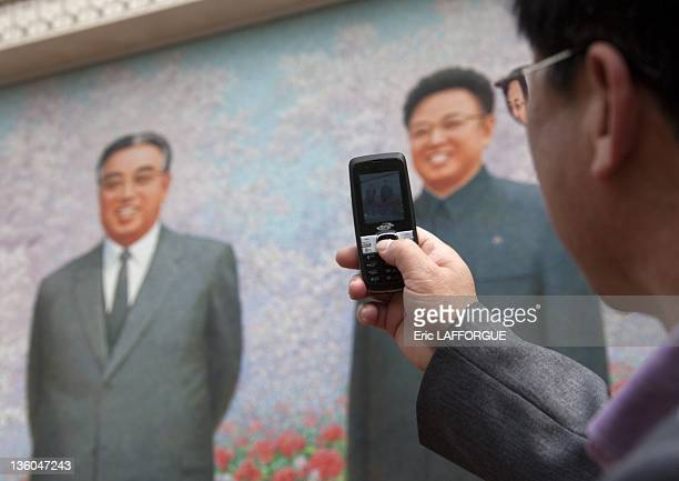 Man taking a picture during the exhibition for the Presidents' birthdays, the two leaders, Kim Il Sung and Kim Jong Il on a giant mosaic on April 25,...