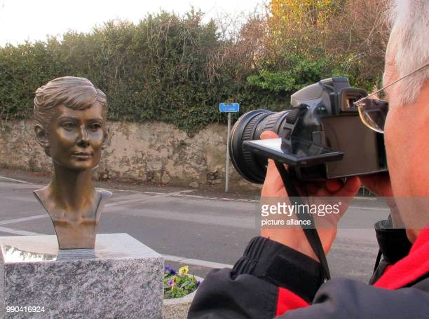 A man taking a picture of a bust representing American actressAudrey Hepburn in Tolochenaz Switzerland 06 January 2018 Hepburn died here 25 years...