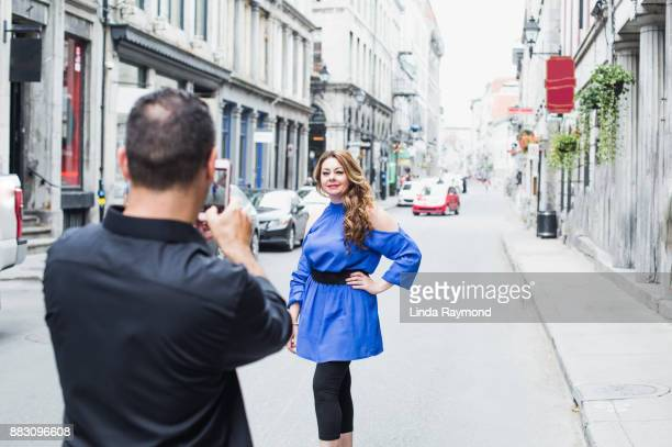 Man taking a picture of a mixed race woman in the street