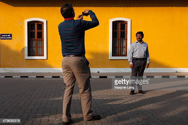 Man taking a picture of another man by the French consulate of Pondicherry. Puducherry is a Union territory enclave in Tamil Nadu, India.