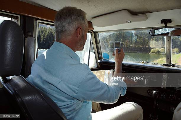 Man taking a picture of lake with mobile phone
