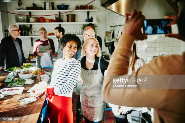 Man taking a picture of smiling friends with smartphone during cooking class