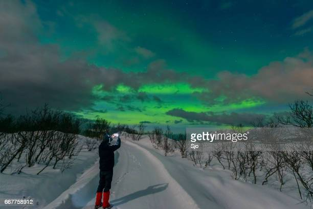 Man taking a picture of the Aurora Northern Polar light