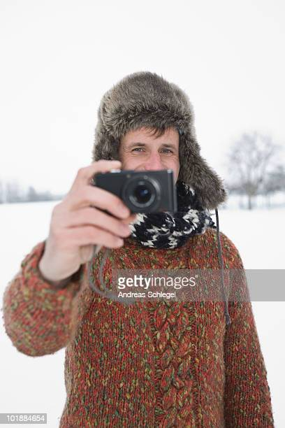 A man taking a picture with a digital camera, outdoors, portrait