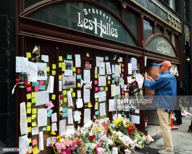 Man taking a picture with his iphone of the flowers, notes, and photos left in memory of Anthony Bourdain, and displayed at the closed location of Brasserie Les Halles in NYC, where Bourdain once worked as the executive chef.