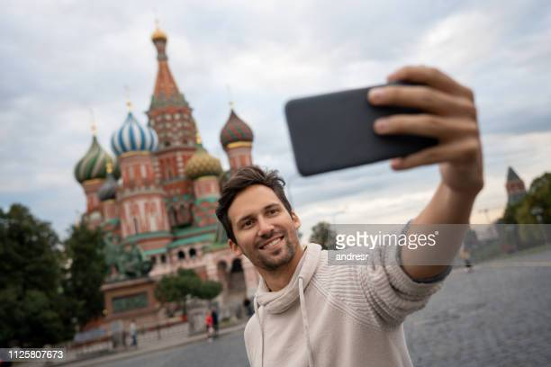 man taking a selfie in moscow at the red square in front of saint basil's cathedral - red square stock pictures, royalty-free photos & images