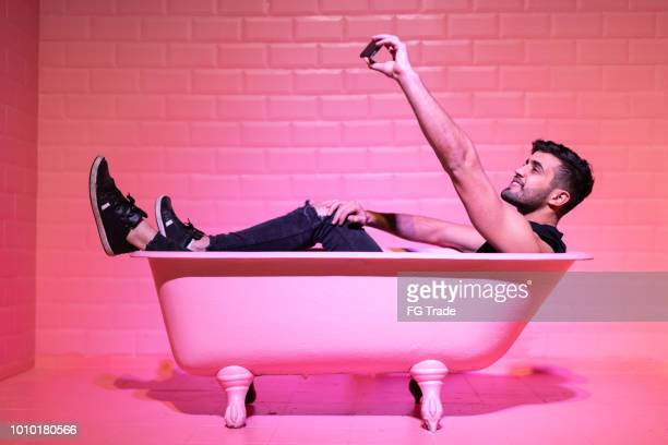 man taking a selfie in the pink bathtube - influencer stock pictures, royalty-free photos & images