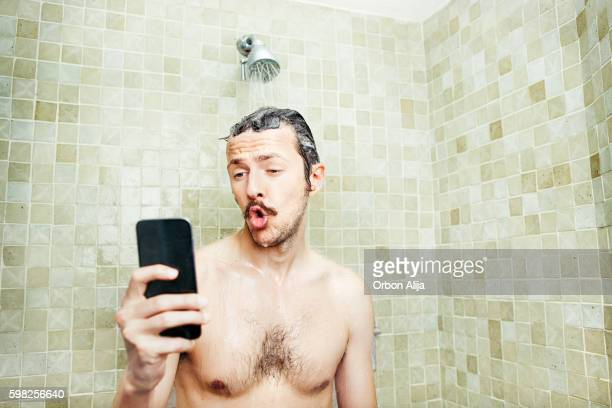 man taking a selfie in the shower - homme sous la douche photos et images de collection