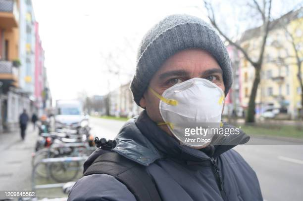 man taking a selfie in the street wearing a protection mask looking at camera. berlin, germany. - 1918 flu pandemic stock pictures, royalty-free photos & images