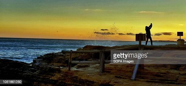 TORREDEMBARRA TARRAGONA SPAIN A man taking a selfie on the cliffs at Roc de San Gaíeta at sunset in Torredembarra Tarragona Spain