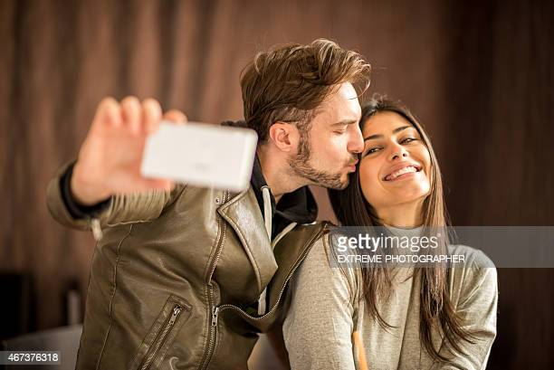Man taking a selfie while kissing his girlfriend