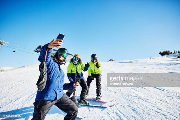 man taking a selfie with friends at top of ski slope on sunny winter afternoon - skiing stock pictures, royalty-free photos & images